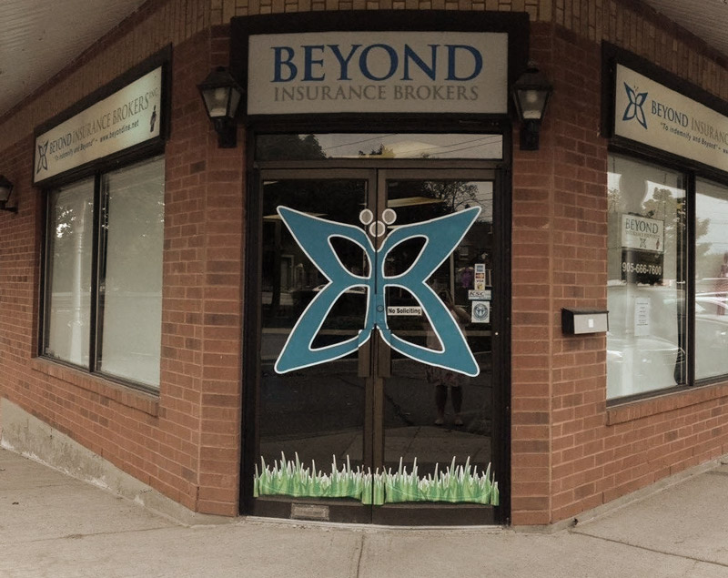 Photo of Beyond Insurance storefront with big logo on the door.